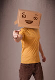 Young man gesturing with a cardboard box on his head with smiley Stock Image
