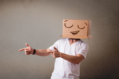 Young man gesturing with a cardboard box on his head with smiley Stock Images