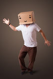 Young man gesturing with a cardboard box on his head with smiley Stock Photo