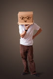 Young man gesturing with a cardboard box on his head with smiley Royalty Free Stock Photography