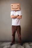Young man gesturing with a cardboard box on his head with smiley Royalty Free Stock Photos
