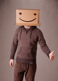 Young man gesturing with a cardboard box on his head with smiley Stock Photography