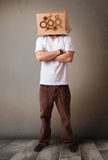 Young man gesturing with a cardboard box on his head with spur w Royalty Free Stock Images
