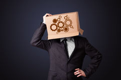 Young man gesturing with a cardboard box on his head with spur w Royalty Free Stock Photo