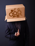Young man gesturing with a cardboard box on his head with spur w Stock Photo