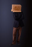 Young man gesturing with a cardboard box on his head with spur w Royalty Free Stock Image