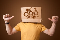 Young man gesturing with a cardboard box on his head with spur w Stock Image