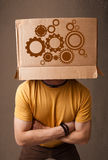 Young man gesturing with a cardboard box on his head with spur w Royalty Free Stock Photography