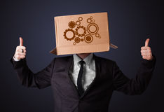 Young man gesturing with a cardboard box on his head with spur w Stock Photography