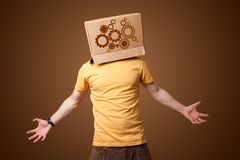 Young man gesturing with a cardboard box on his head with spur wheels. Young man standing and gesturing with a cardboard box on his head with spur wheels Stock Photos