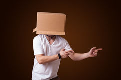 Young man gesturing with a cardboard box on his head Stock Photo