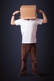 Young man gesturing with a cardboard box on his head Royalty Free Stock Photos