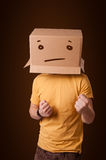 Young man gesturing with a cardboard box on his head with straig Stock Image