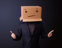 Young man gesturing with a cardboard box on his head with straig Royalty Free Stock Photo