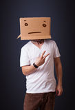 Young man gesturing with a cardboard box on his head with straig Royalty Free Stock Images