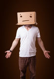 Young man gesturing with a cardboard box on his head with straig Stock Photos