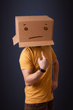 Young man gesturing with a cardboard box on his head with straig Royalty Free Stock Photos