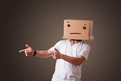 Young man gesturing with a cardboard box on his head with straig Royalty Free Stock Photography