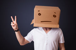 Young man gesturing with a cardboard box on his head with straig Royalty Free Stock Image