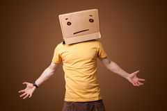 Young man gesturing with a cardboard box on his head with straig Stock Images