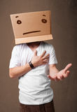 Young man gesturing with a cardboard box on his head with straig Stock Photo