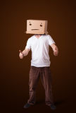 Young man gesturing with a cardboard box on his head with straig Stock Photography
