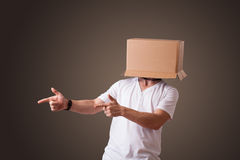 Young man gesturing with a cardboard box. Young man standing and gesturing with a cardboard box on his head Stock Photo