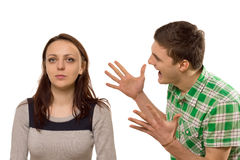 Young man gesturing at his girlfriend. Young men gesturing and shouting at his girlfriend in frustration as she feigns complete indifference looking ahead with a Stock Image