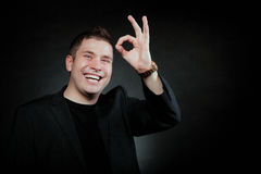 Young man gesturing the ok okay hand sign. Happy Satisfied man gesturing the all right symbol, showihg ok sign black background Stock Image