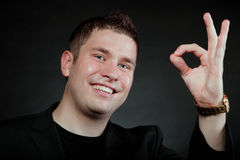Young man gesturing the ok okay hand sign. Happy Satisfied man gesturing the all right symbol, showihg ok sign black background Stock Photo
