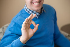 Young man gesturing OK sign. Casual attractive happy young man gesturing ok sign indoors, close-up of hand Royalty Free Stock Photo