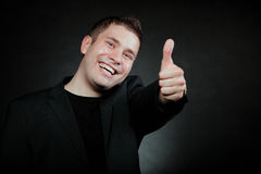 Young man gesturing the ok sign. Happy man giving thumb up gesturing the all right symbol , ok sign black background Stock Photos