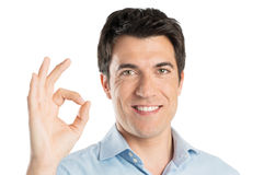 Young Man Gesturing Ok Sign. Satisfied Positive Man Gesturing Ok Sign Isolated On White Background Stock Photo
