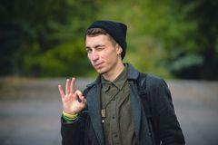 Young man gesturing OK sign and winks against gray background. Happy young man gesturing OK sign and winks against green background Stock Photography