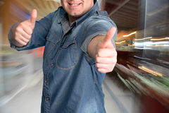 Young man gesturing thumbs up at shopping mall Royalty Free Stock Images