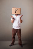 Young man gesturingwith a cardboard box on hishead Stock Photo