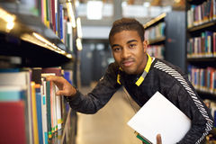 Young man getting books from a public library shelf. Young afro american man getting books from a public library shelf. University student at library for Stock Photography