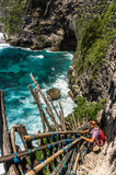 Young man getting down the cliff to beautiful cove Stock Photography