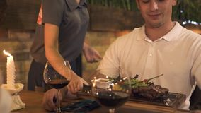 Young man getting food in restaurant while evening dinner with girlfriend. Waitress putting meat plate on table for man. While romantic evening in trendy cafe stock footage