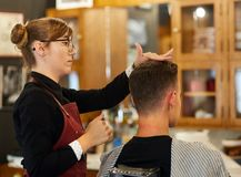 Young man getting a haircut. Young men getting a short trendy haircut in the barber shop Stock Photography