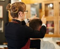Young man getting a haircut. Young men getting a short trendy haircut in the barber shop Stock Photos