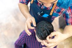Young Man Getting a Hairstyle in a Barbershop royalty free stock photography