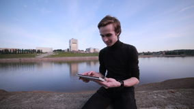 Young man getting message with tablet computer near the city lake. HD stock footage