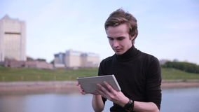 Young man getting message with tablet computer near the city lake. HD stock video