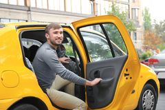 Young man getting out of taxi. Car Stock Image
