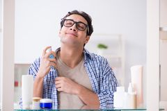 The young man is getting prepared for working day in bathroom. Young man is getting prepared for working day in bathroom Royalty Free Stock Image
