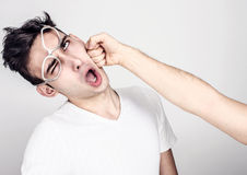 Young man getting punched in the jaw. Stock Image