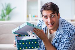 The young man getting rabbit as birthday present. Young man getting rabbit as birthday present Royalty Free Stock Photo