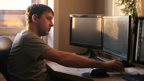 A young man getting ready for work at the computer on the sunset background, takes a notebook in hand, 4k stock video footage