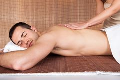 Young man getting shoulder massage Stock Photos